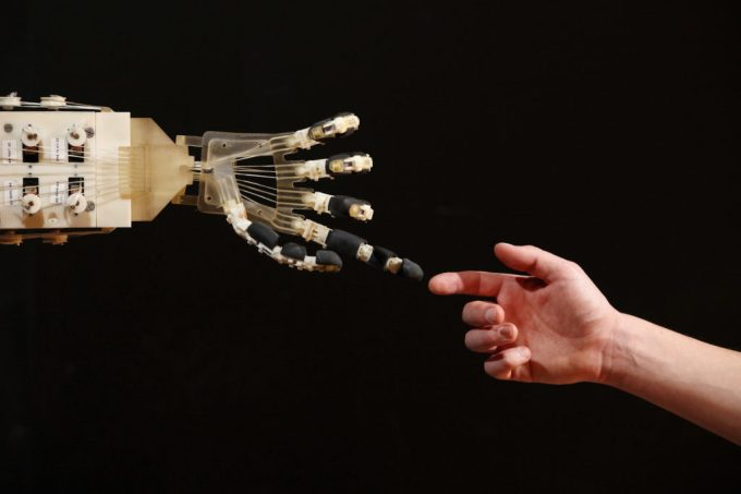 LONDON, ENGLAND - NOVEMBER 29:  Robotics student Gildo Andreoni interacts with a Dexmart robotic hand built at the University of Bologna in the Robotville exhibition at the Science Museum on November 29, 2011 in London, England. The Science Museum's Robotville exhibition showcases 20 unique and cutting-edge robots from European research laboratories, it  is free to enter and runs from December 1-4, 2011.  (Photo by Oli Scarff/Getty Images)